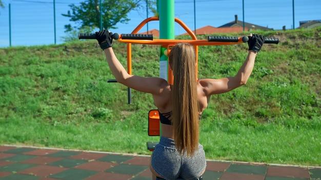 Mulher irreconhecível treinando de volta usando o simulador ao ar livre