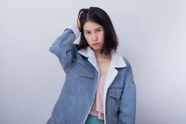 Mulher irritada asiática nova que sente a emoção negativa e má que veste o retrato azul da roupa ocasional