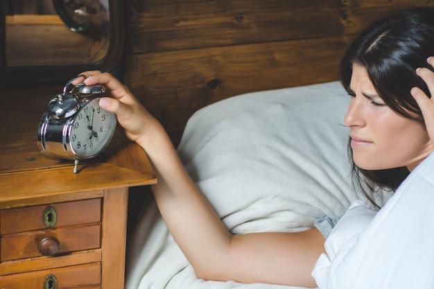 Mulher irritada com despertador