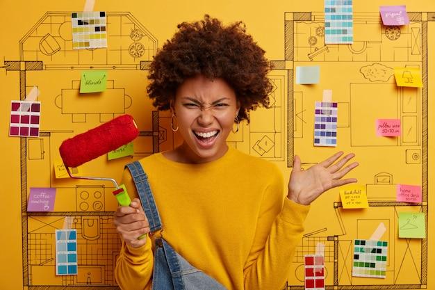 Mulher irritada com penteado afro encaracolado, levanta a palma da mão, segura rolo de pintura, reforma paredes, veste-se casualmente, se opõe ao projeto de design da casa