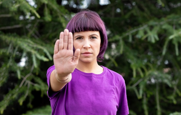 Mulher irritada com roxo mostrando a palma da mão dizendo parar