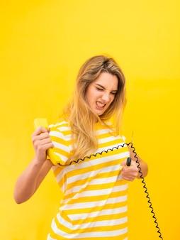 Mulher irritada, cortar o fio de telefone