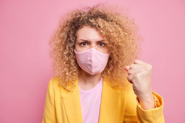 Mulher irritada de cabelos cacheados descontente fecha o punho com raiva toma precauções durante a pandemia usa máscara protetora para proteger sua vida saudável vestida com roupas formais poses em ambientes fechados