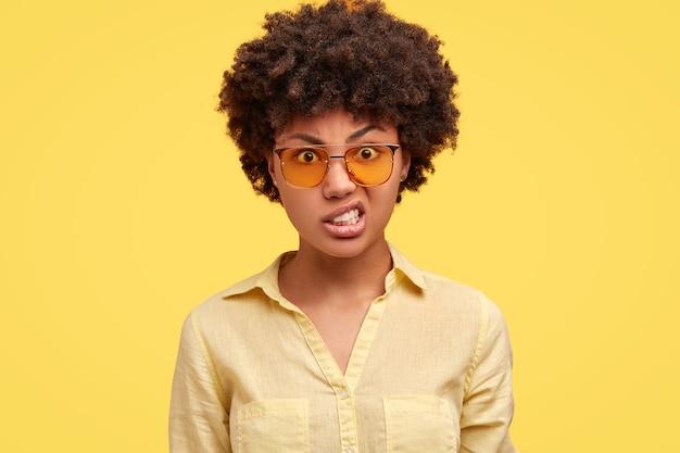 Mulher irritada de óculos escuros trinca os dentes, parece estressada e com expressão irritada, levanta as sobrancelhas, ouve algo desagradável,