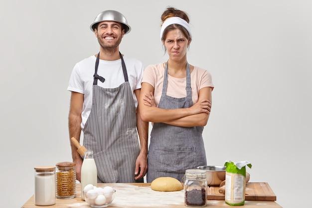 Mulher irritada descontente fica de mãos cruzadas, suja de farinha, homem feliz de avental fica perto, cozinham juntos na cozinha, preparam massa para pão, ficam em casa, cansados de assar e do processo culinário