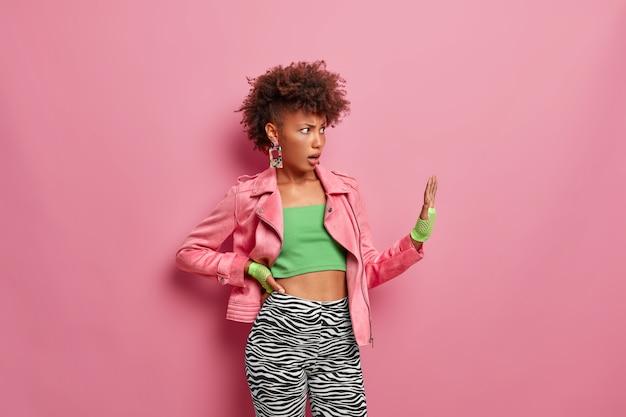 Mulher irritada e descontente faz gesto de parar, mantém a palma da mão voltada para a frente em gesto de recusa, pede para não se aproximar, vestida com roupas esportivas estilosas