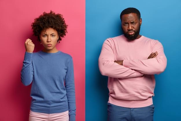 Mulher irritada e insatisfeita fecha o punho e mostra seu poder, homem negro com a barba por fazer fica perto com os braços cruzados e expressa emoções negativas