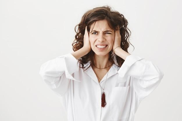 Mulher irritada e irritada fechando os ouvidos com barulho alto