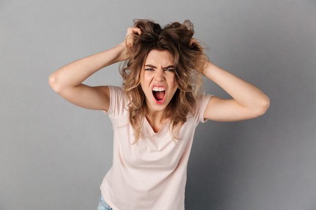 Mulher irritada em t-shirt gritando e segurando o cabelo dela enquanto mais cinza