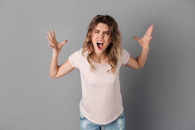 Mulher irritada em t-shirt gritando sobre cinza