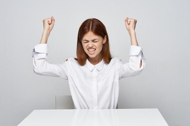 Mulher irritada em uma camisa branca sobre um fundo claro