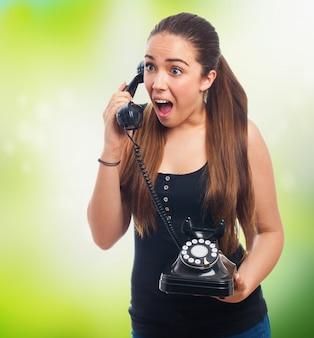Mulher irritada falando em um telefone antigo