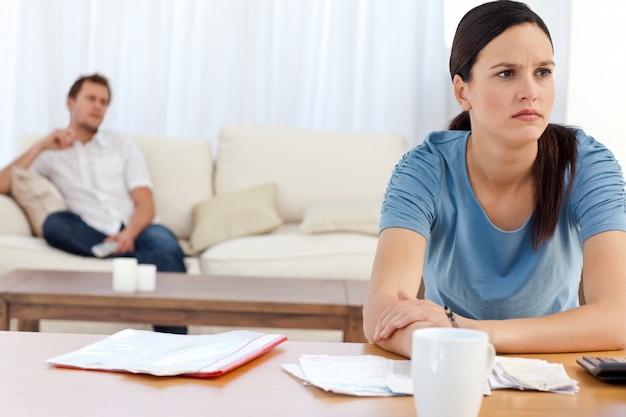 Mulher irritada fazendo sua conta enquanto seu namorado está relaxando