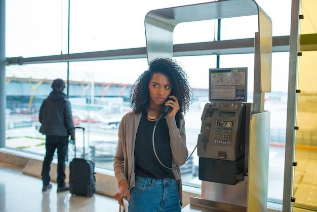 Mulher irritada no aeroporto falando por telefone público