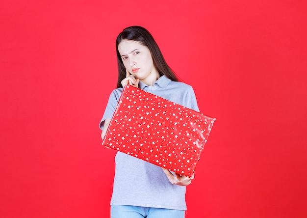 Mulher irritada segurando uma caixa de presente e olhando para a câmera