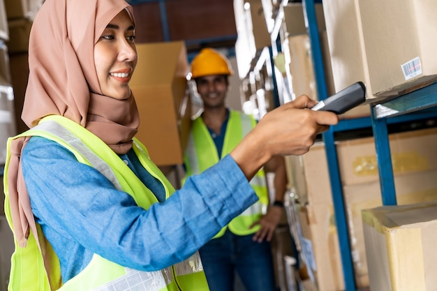 Mulher islâmica asiática em depósito, fazendo inventário com leitor de código de barras