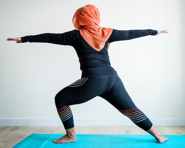 Mulher islâmica fazendo yoga no quarto