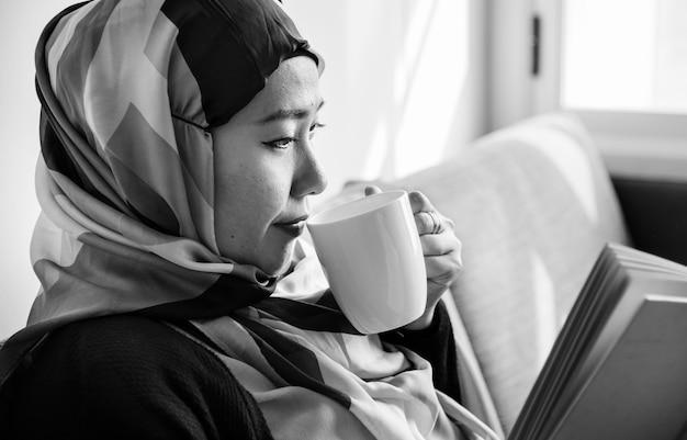 Mulher islâmica lendo e bebendo café