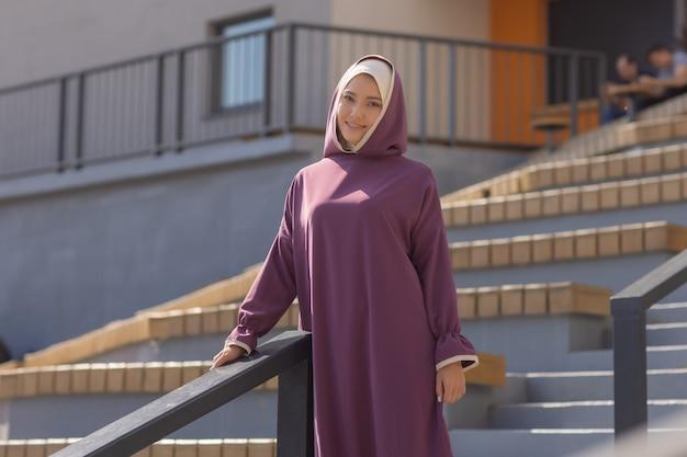 Mulher islâmica linda em um vestido muçulmano de pé em um parque de verão rua fundo floresta outono ...