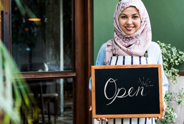 Mulher islâmica, pequeno, proprietário negócio, segurando, quadro-negro, com, sorrindo