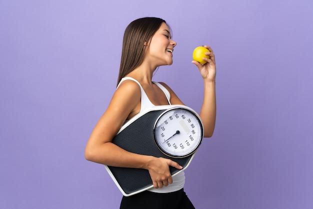 Mulher isolada em roxo com máquina de pesar e com uma maçã