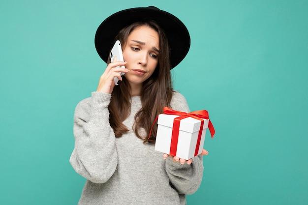Mulher isolada sobre a parede de fundo azul, usando chapéu preto e suéter cinza segurando uma caixa de presente, falando no celular e olhando para o lado.