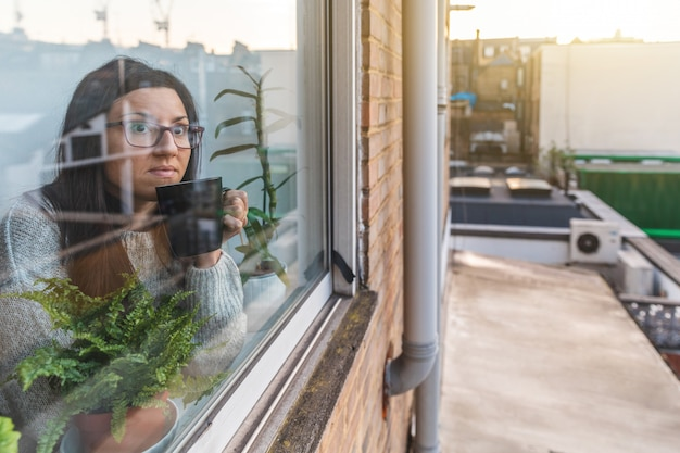 Mulher isolando em casa sozinha e olhando pela janela