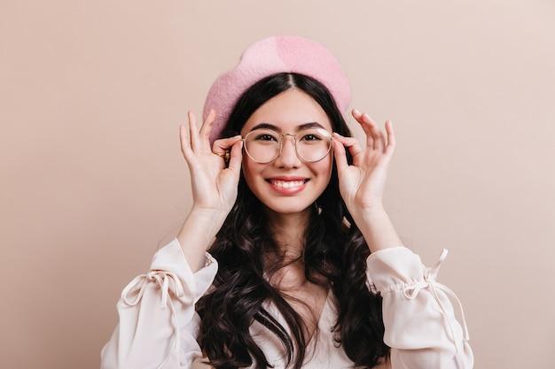 Mulher japonesa animada posando em copos. linda mulher asiática na boina rindo de câmera.