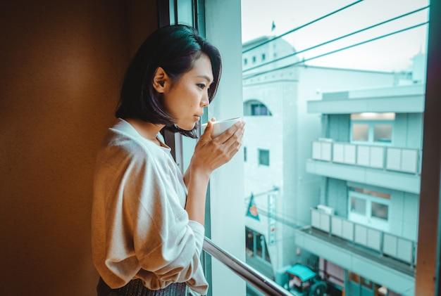 Mulher japonesa bebe chá e olha pela janela