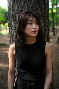 Mulher japonesa com tiro médio perto de uma árvore