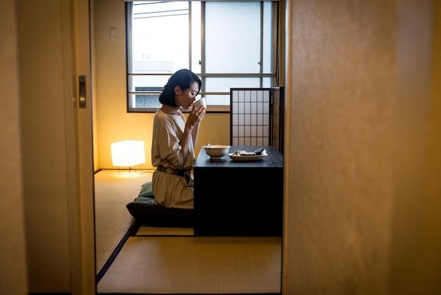 Mulher japonesa comendo em um apartamento tradicional