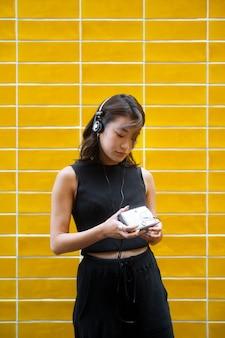 Mulher japonesa de tiro médio com fones de ouvido