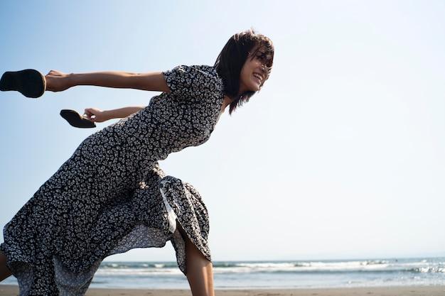 Mulher japonesa de tiro médio correndo na praia