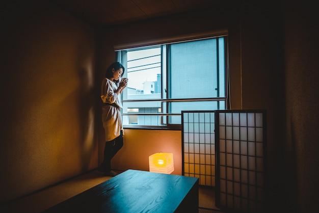 Mulher japonesa em casa bebe chá