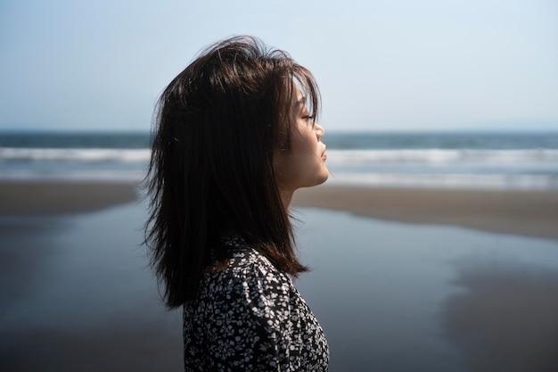 Mulher japonesa em tiro médio à beira-mar