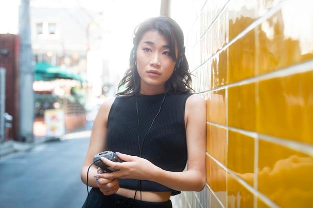 Mulher japonesa ouvindo música tiro médio