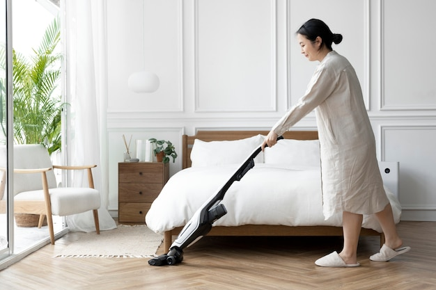 Mulher japonesa passando aspirador no quarto