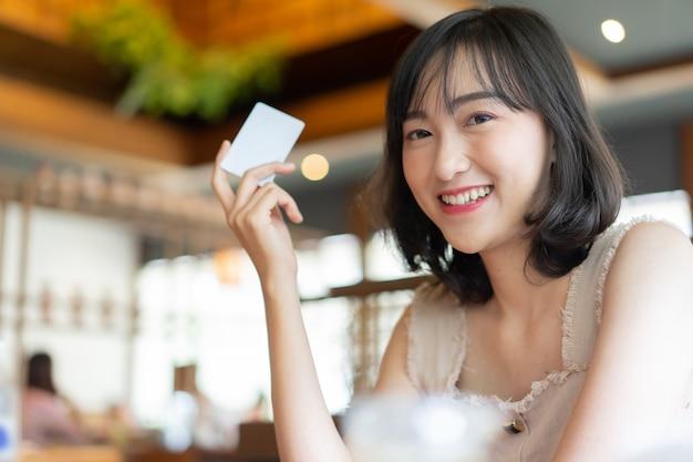 Mulher japonesa sorrindo e mão mostrando o cartão de crédito no restaurante
