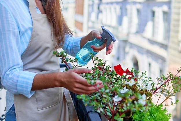 Mulher jardineira regando flores na varanda usando spray