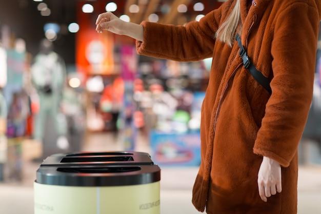 Mulher joga objeto na lata de lixo. modelo com espaço vazio.