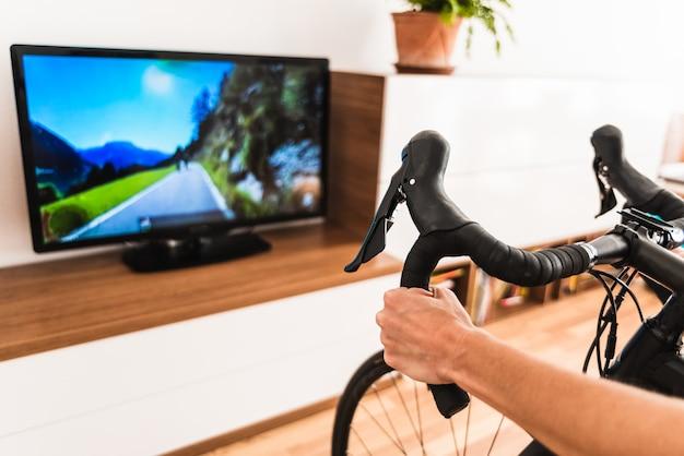 Mulher joga um jogo de bicicleta online na sala de estar de sua casa, suando enquanto faz exercícios de pedalada conectada à internet em sua smart tv.
