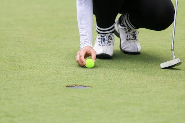 Mulher jogadora de golfe jogando no gramado