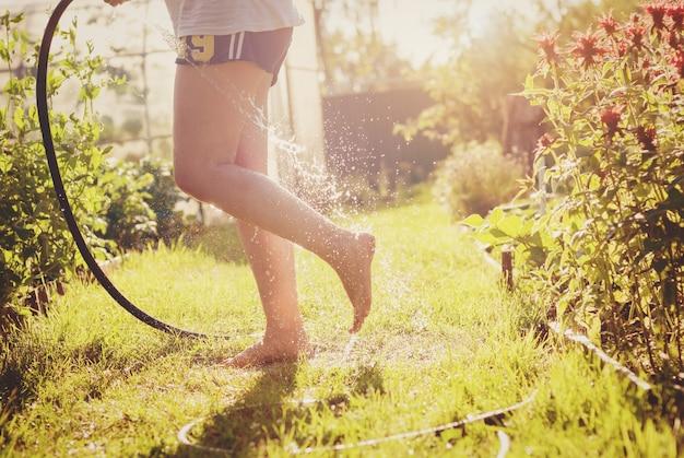 Mulher jogando água nos pés com uma mangueira de jardim no quintal, se divertindo em um dia quente de verão