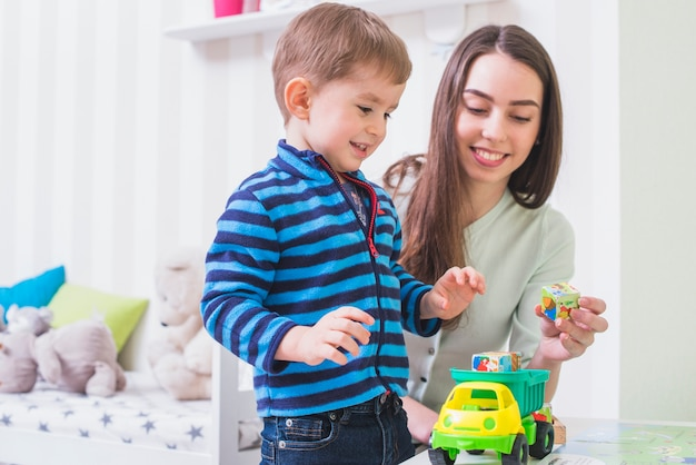 Mulher, jogando carro brinquedo, com, filho