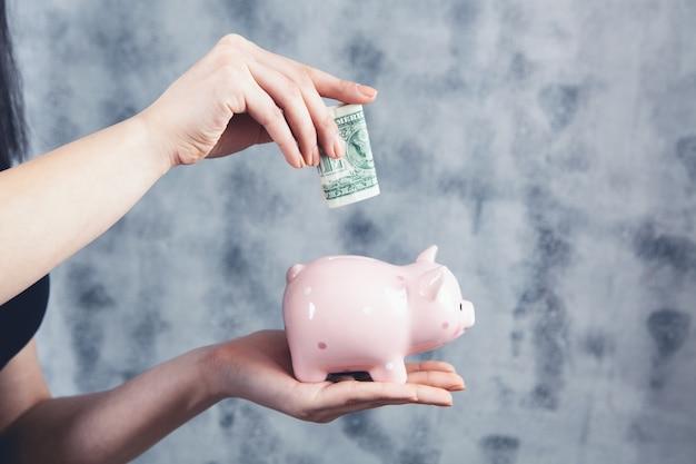 Mulher jogando dólar no cofrinho cinza