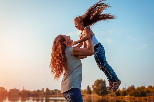 Mulher jogando e se divertindo com a filha no parque de verão ao pôr do sol.