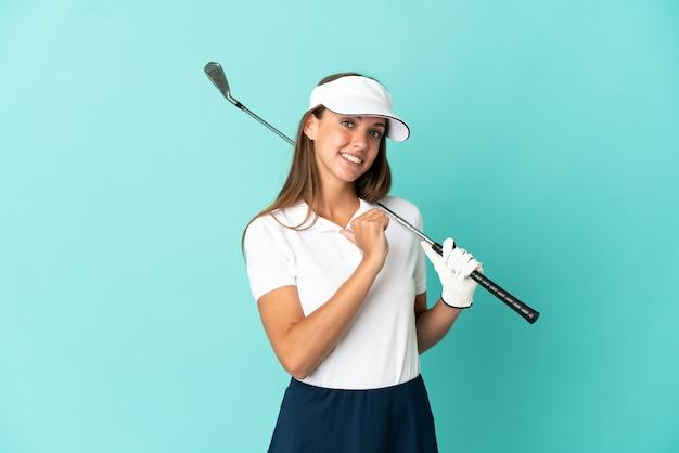 Mulher jogando golfe sobre fundo azul isolado, orgulhosa e satisfeita