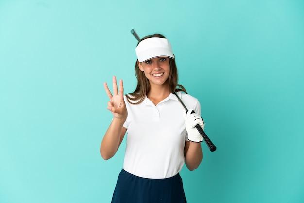 Mulher jogando golfe sobre um fundo azul isolado feliz e contando três com os dedos