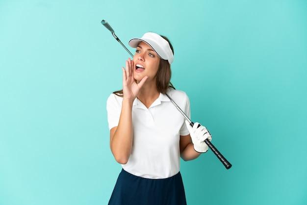 Mulher jogando golfe sobre um fundo azul isolado gritando com a boca bem aberta para o lado