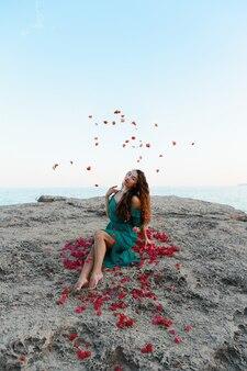 Mulher jogando pétalas de rosa vermelhas perto do mar
